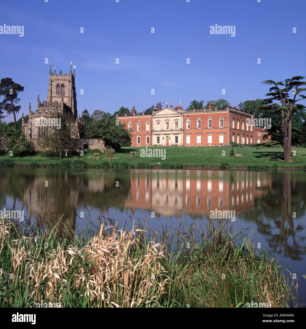 Still waters of lake reflecting views of  Staunton Harold Hall and the commonwealth period Holy Trinity Chapel gothic church Leicestershire England UK - Stock Image