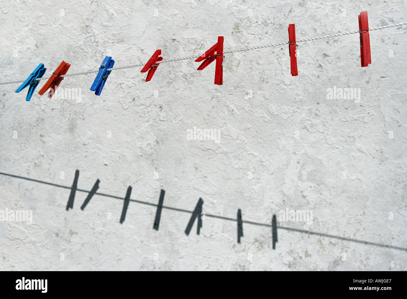 Colored plastic clothespins hanging from a clothes line - Stock Image