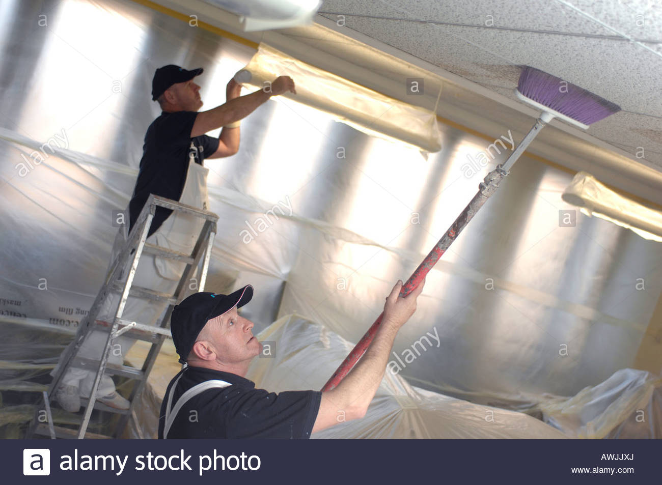 decorators office furniture. Painters And Decorators Cleaning Office Furniture Prior To Spraying Paint - Stock Image S