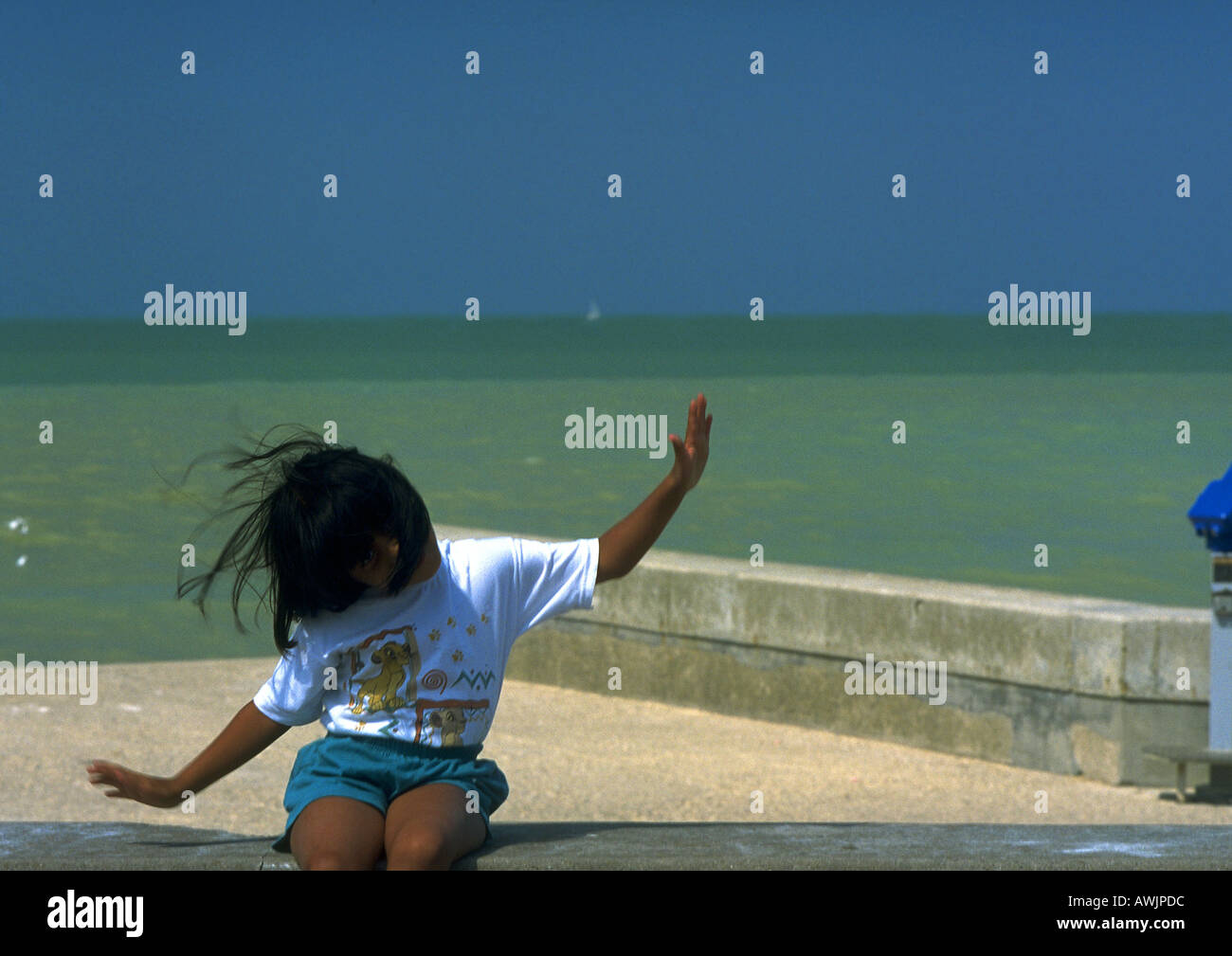 Girl sitting near sea - Stock Image