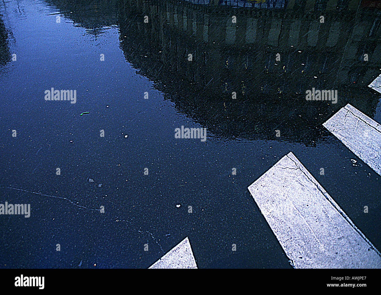 Building reflected on wet ground near cross-walk - Stock Image