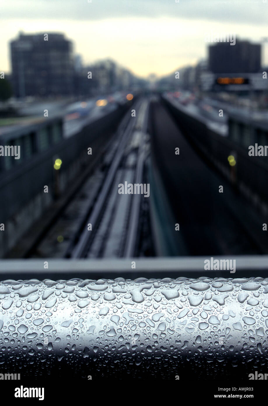 Water drops on rail overlooking traintracks - Stock Image