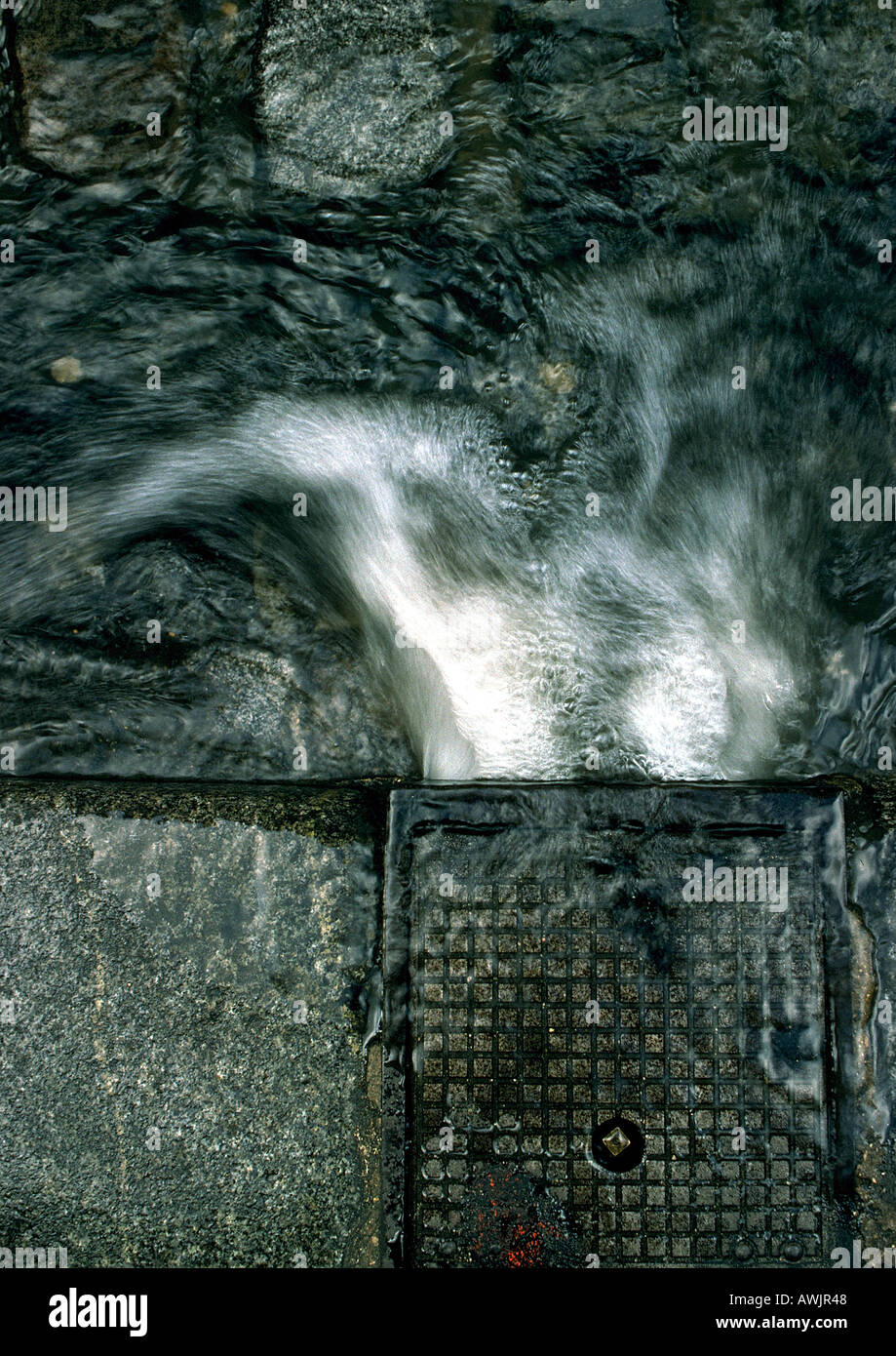 Water pouring into gutter, high angle view, close-up - Stock Image