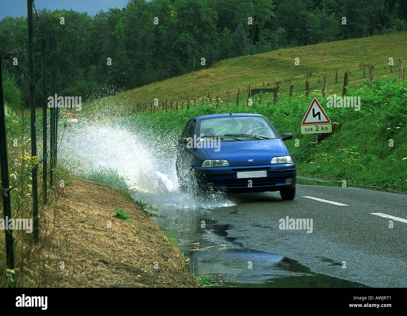 Car driving through puddle, splashing water - Stock Image