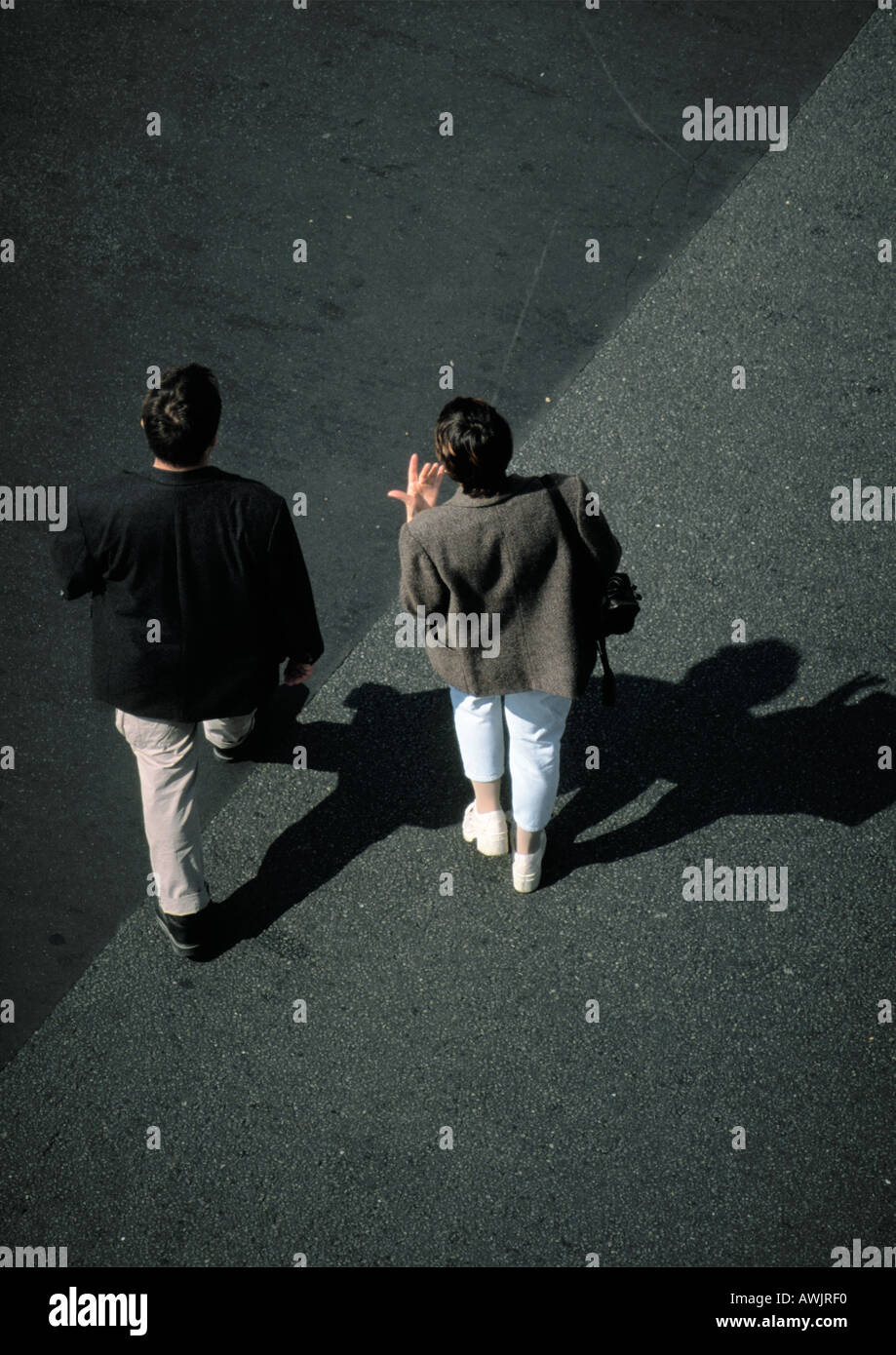 Two people walking on asphalt, high angle view Stock Photo