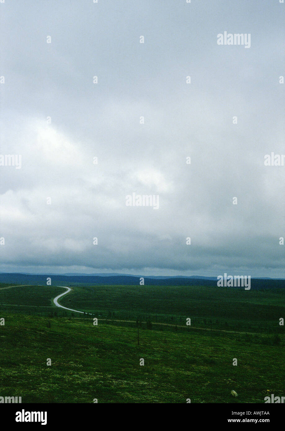 Iceland, road through plain under cloudy sky - Stock Image
