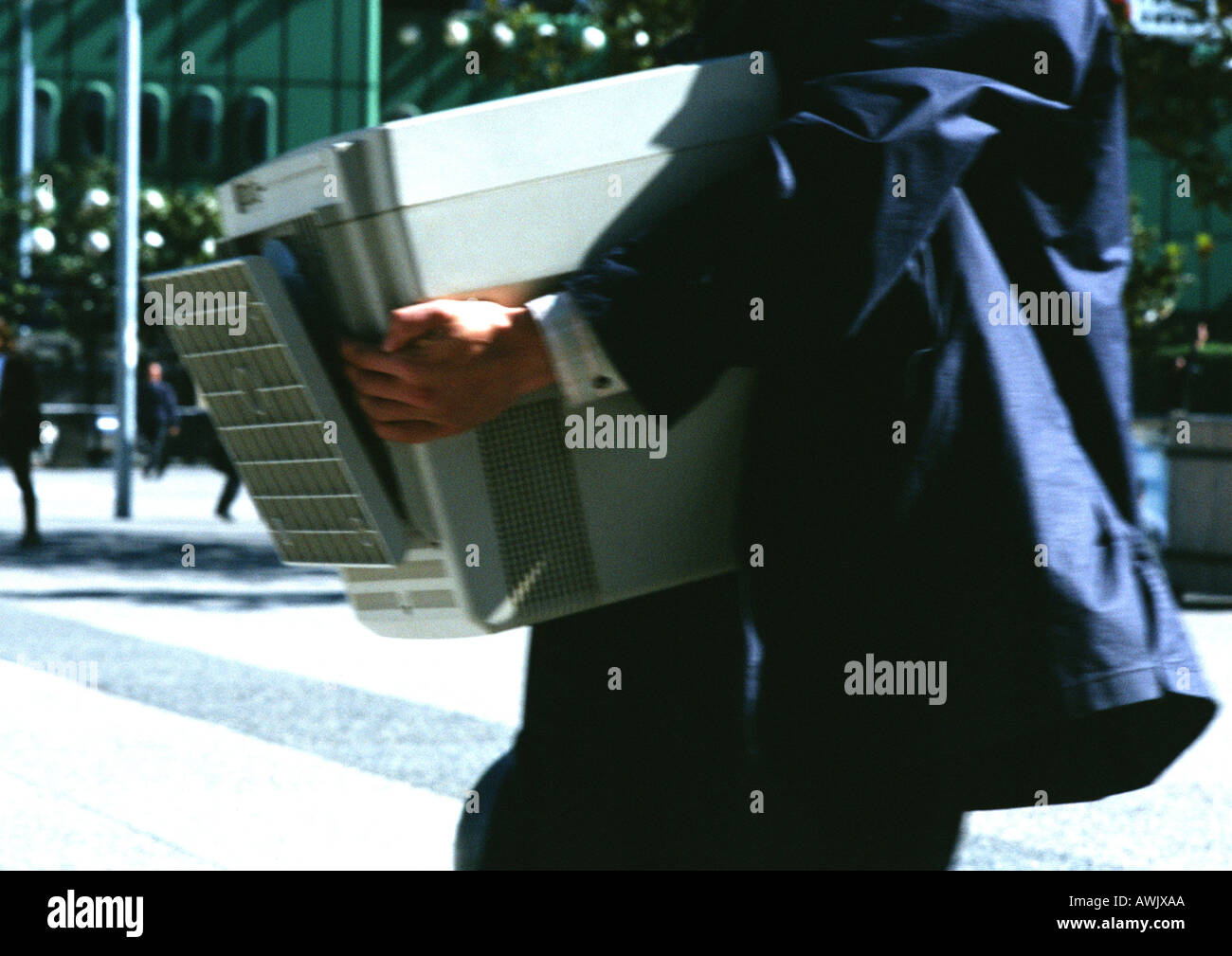 Businessman carrying computer monitor, mid section, close up, blurred. - Stock Image