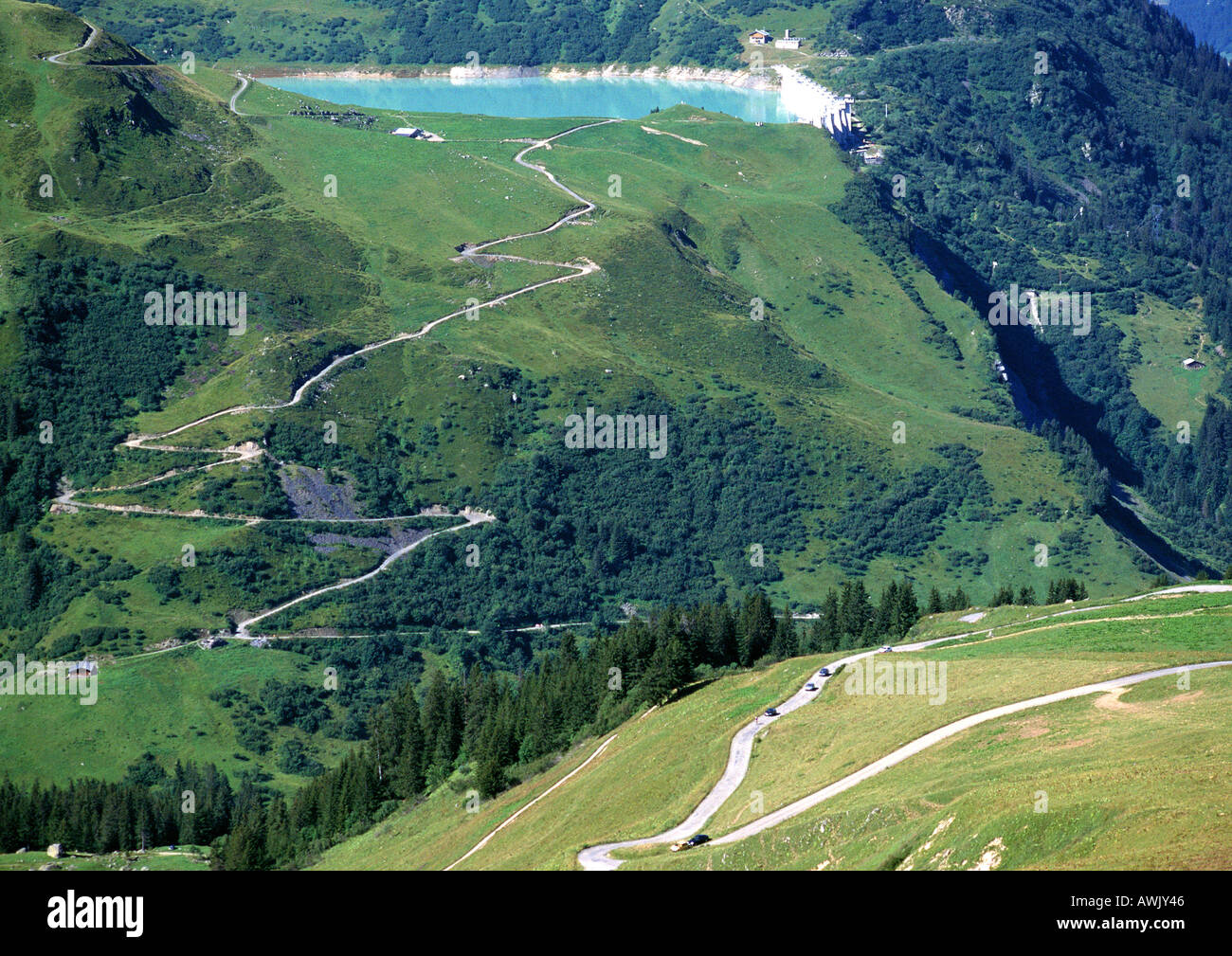 France, Savoie, roads through mountains, one leading to blue lake - Stock Image