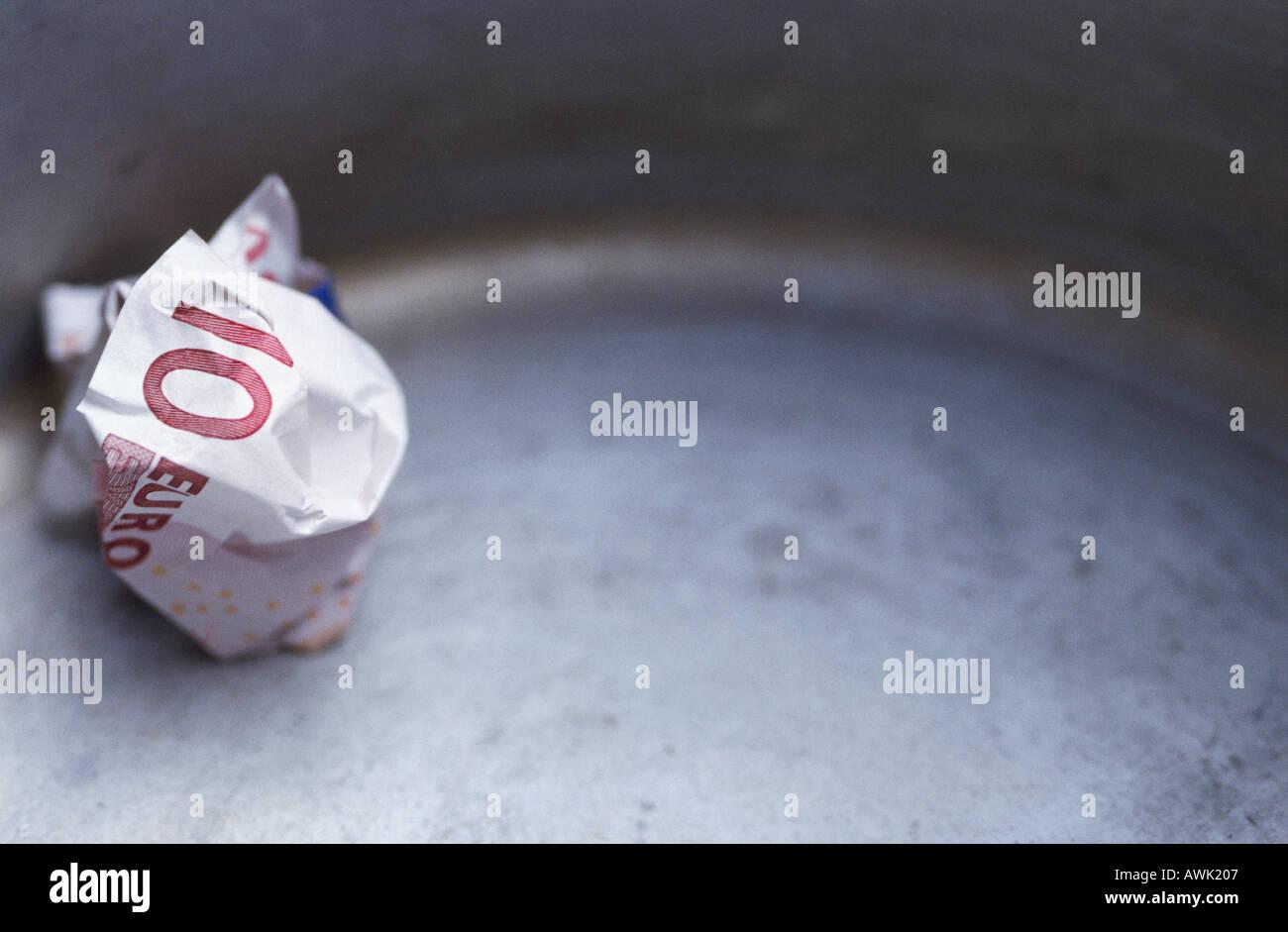 Close-up of ten Euro banknote in garbage bin - Stock Image