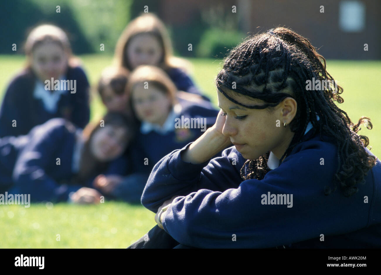 high school girl of mixed race origin in uniform being tormented by group of peers in school playground - Stock Image