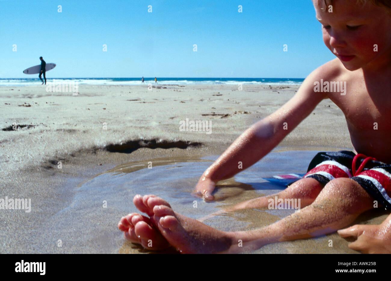 Boy playing at beach - Stock Image