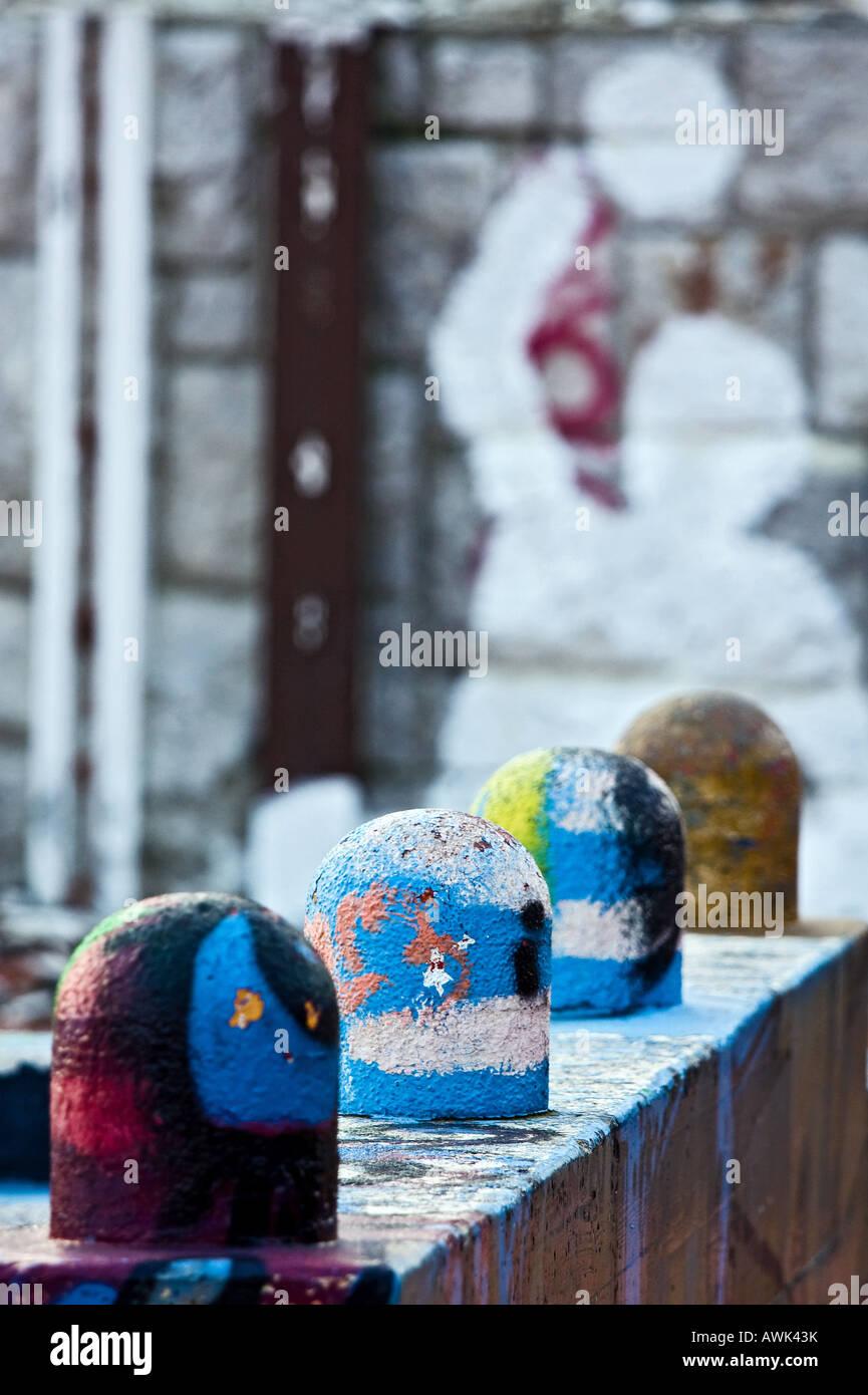Four small grafitti paintedc olumns - Stock Image