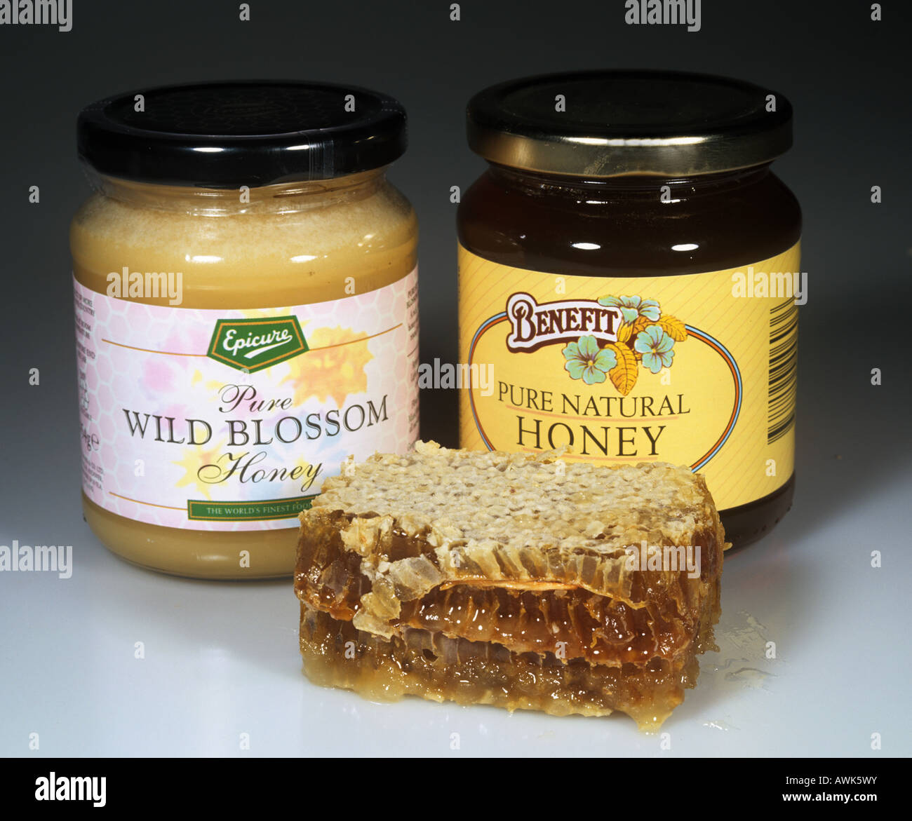 Jars of clear and opaque honey with a slice from a comb from the beehive - Stock Image
