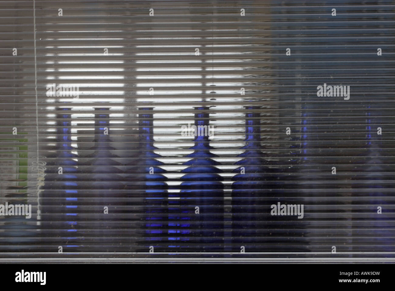 A collection of backlit blue bottles refracted in occluded window glass. - Stock Image