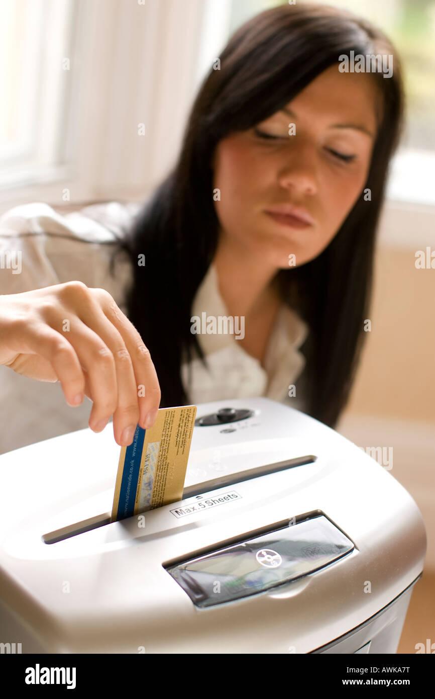 woman shredding credit card - Stock Image