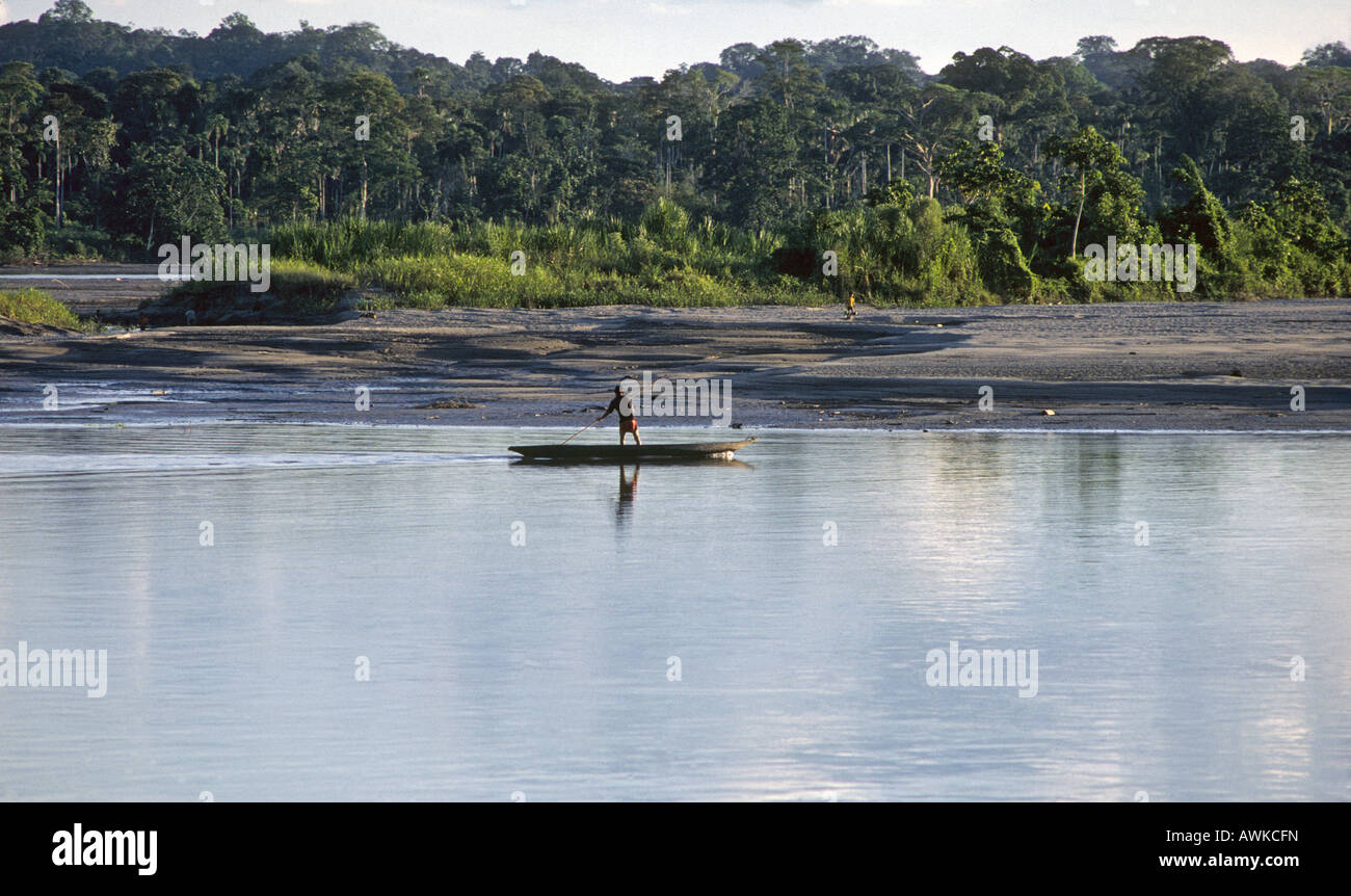 An Indian fisherman poles a dugout canoe down a river in the rain forest in the northern section of Manu National - Stock Image