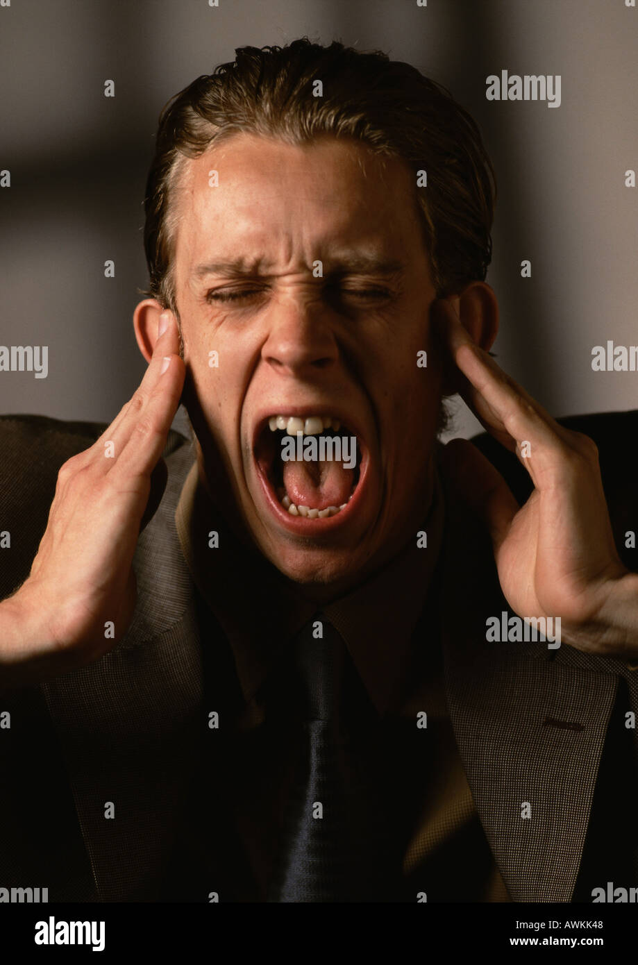 Man covering ears and screaming - Stock Image