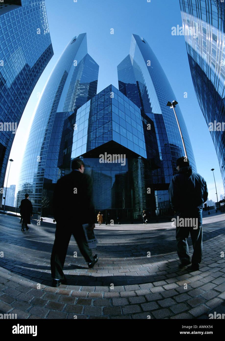 People walking toward skyscrapers - Stock Image