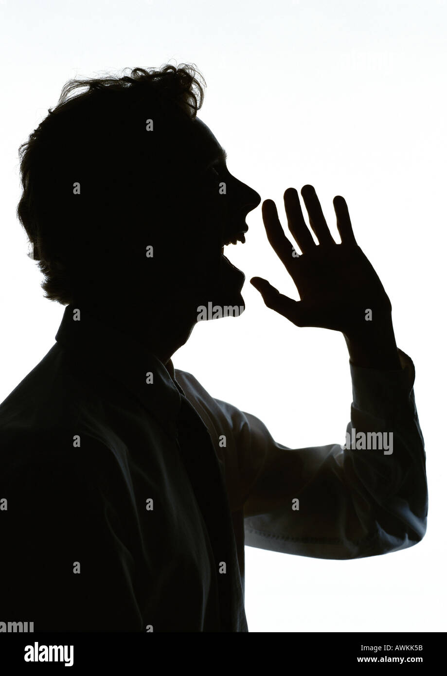 Man yelling with hand out in front of mouth, silhouette - Stock Image