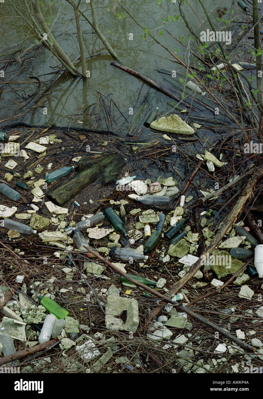 Riverbank polluted with trash Stock Photo