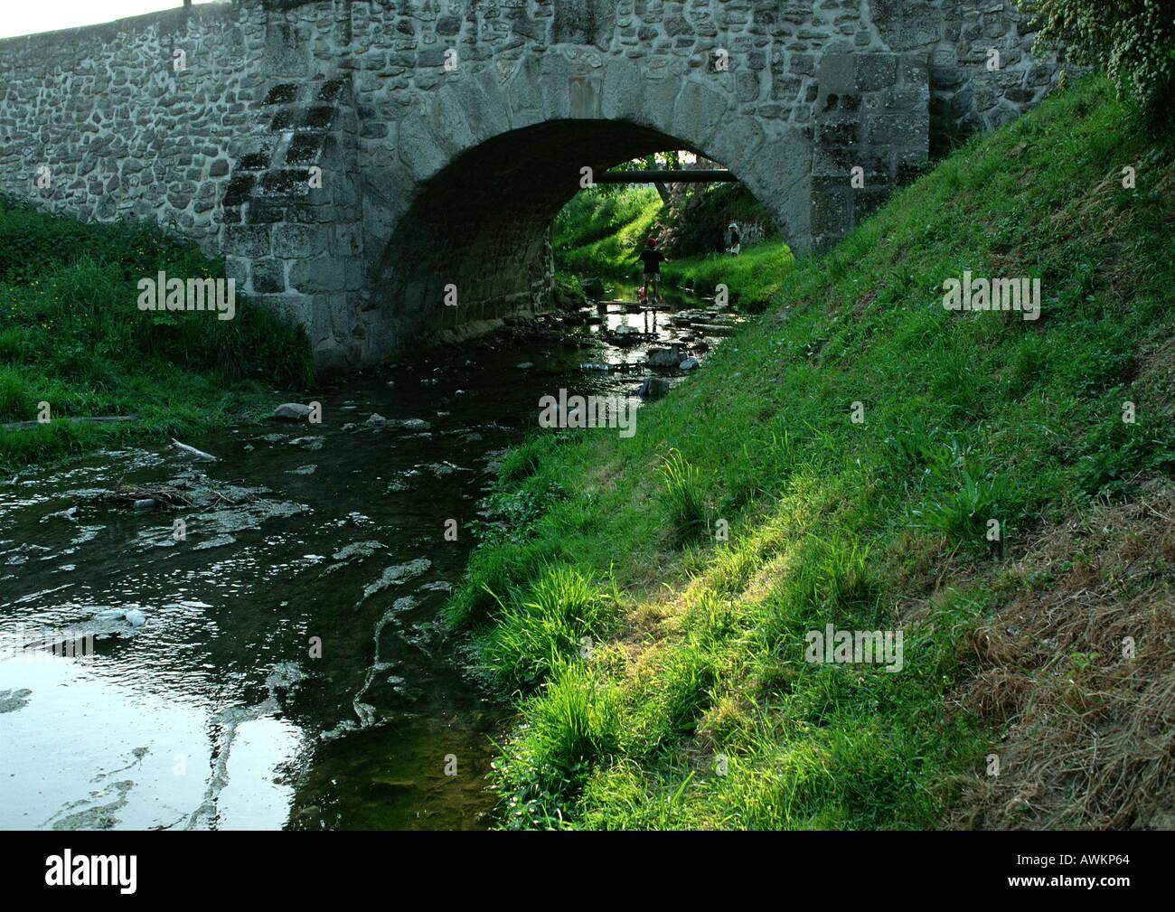 Polluted water running under bridge - Stock Image