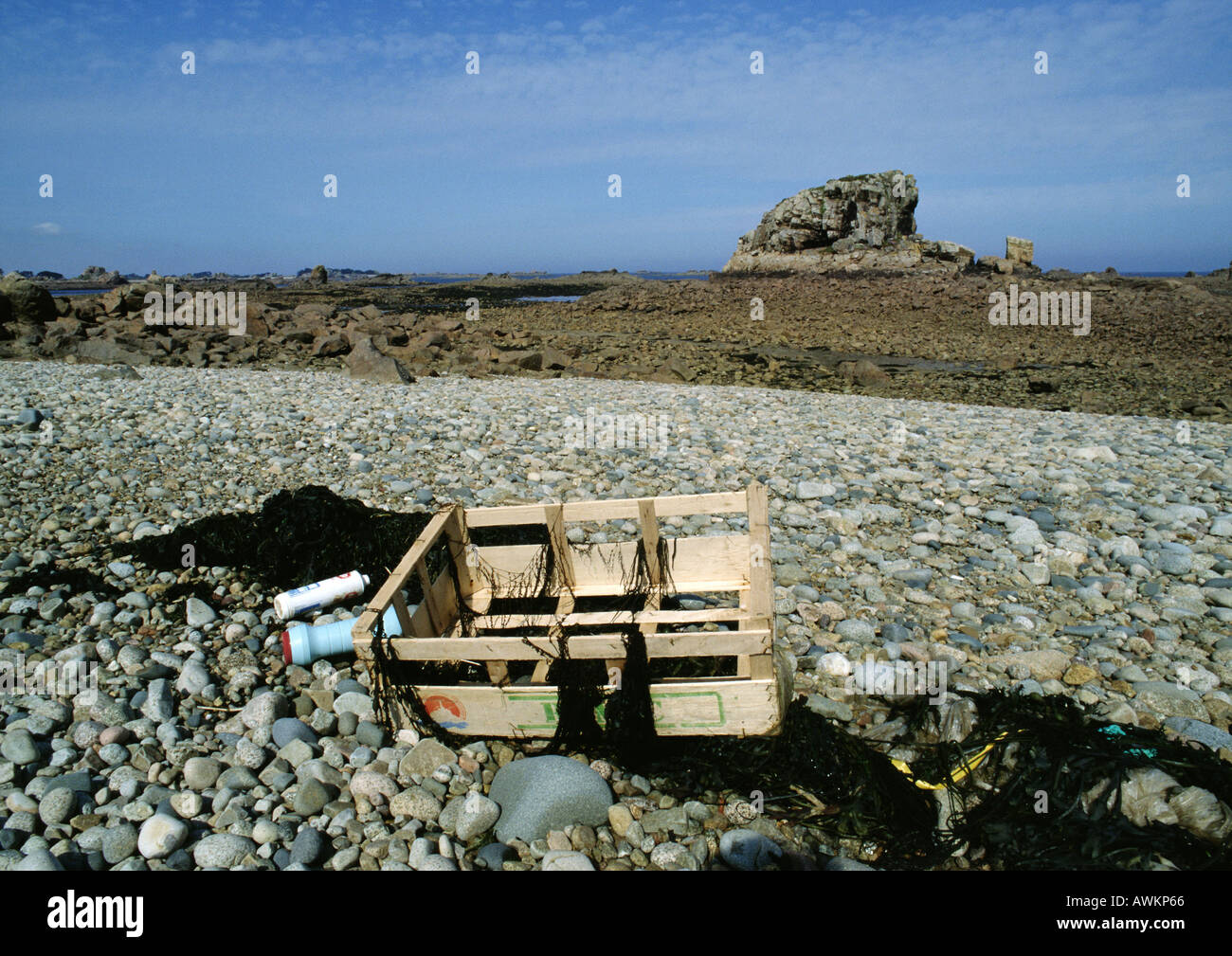 Trash scattered on rocky beach - Stock Image