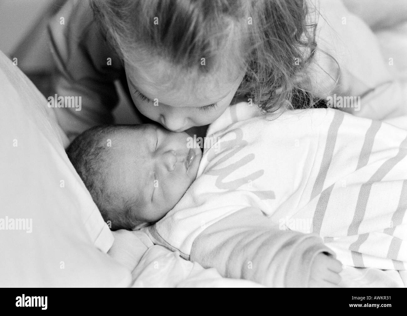 Girl kissing baby, b&w - Stock Image