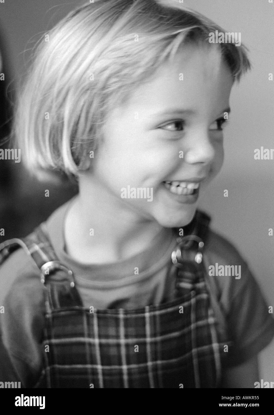 Little girl smiling, looking away, portrait, b&w - Stock Image