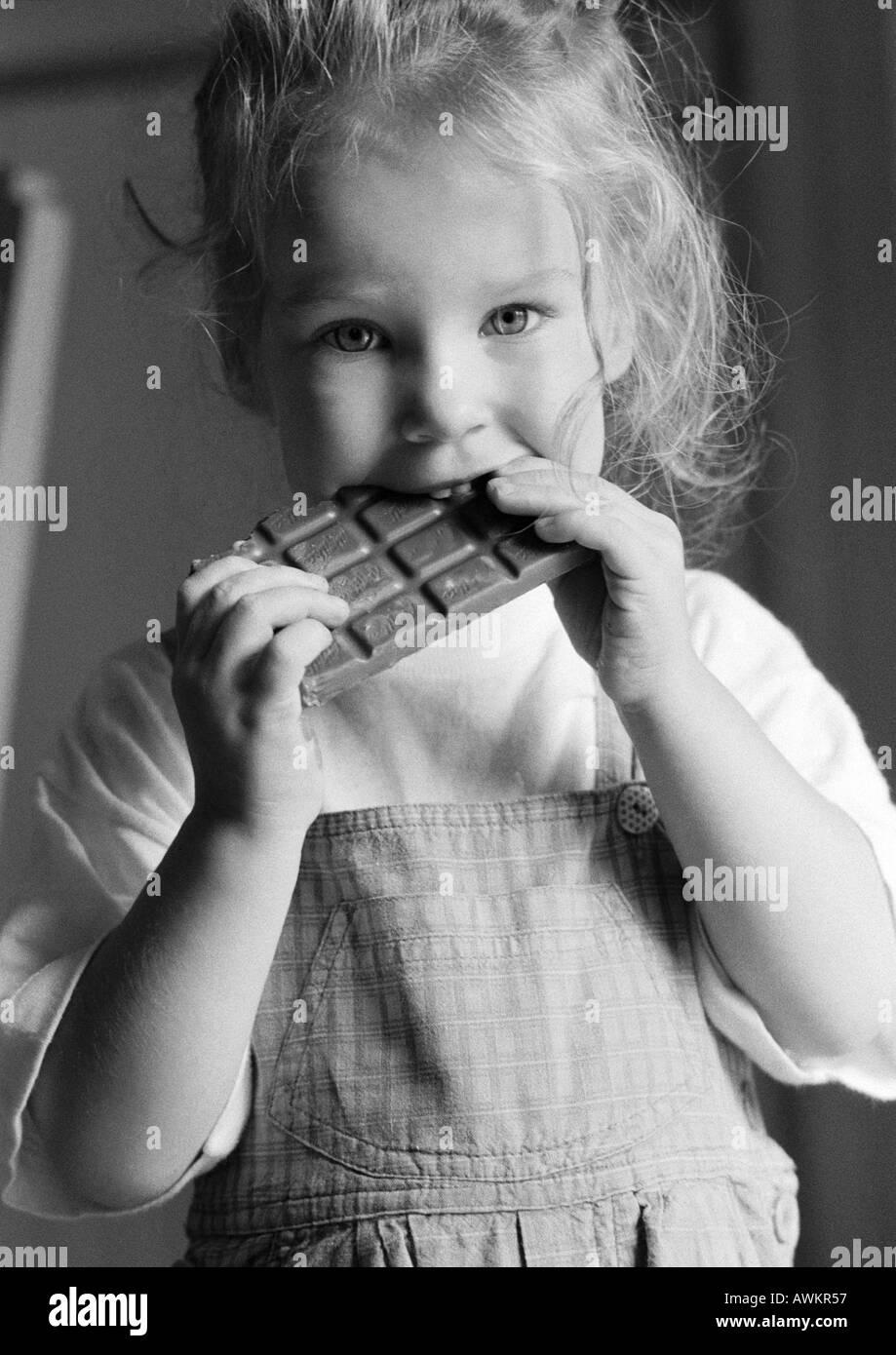 Girl eating chocolate bar, b&w - Stock Image