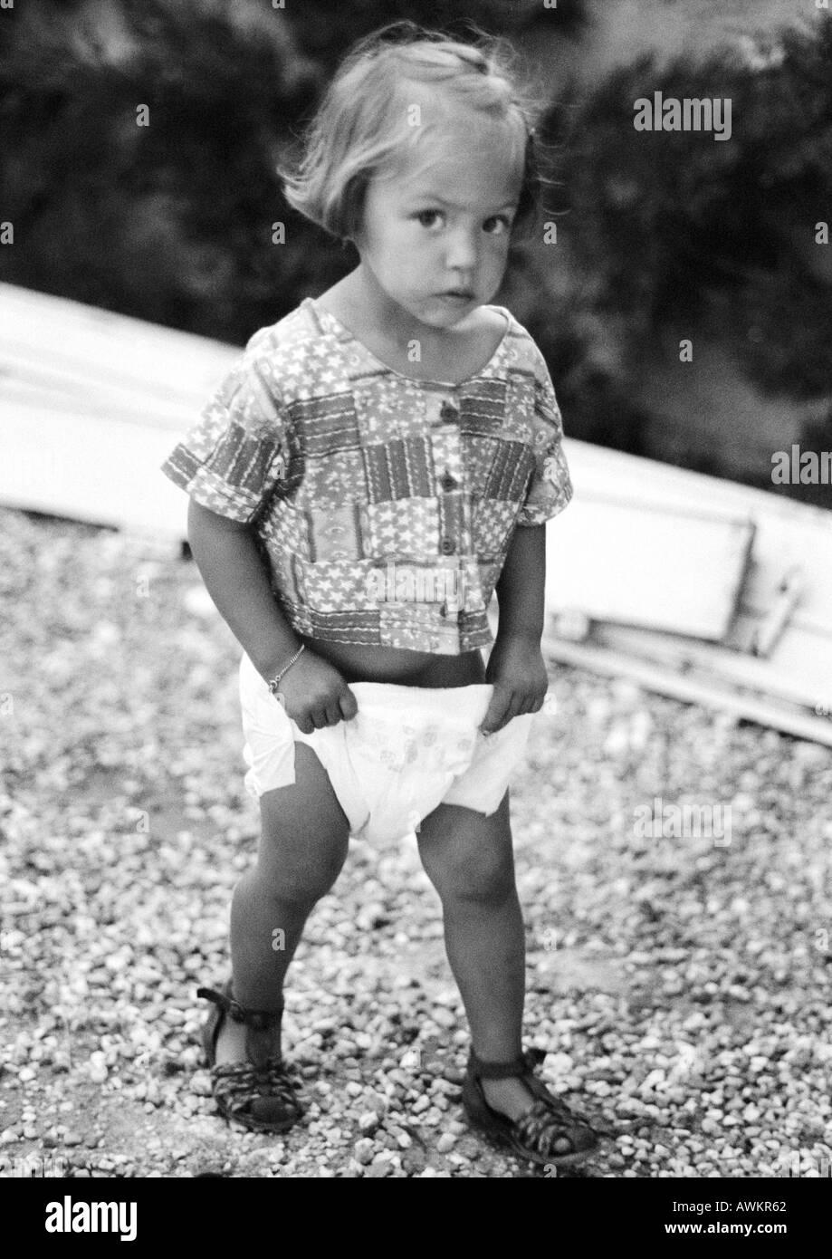 Little girl holding diaper, b&w - Stock Image