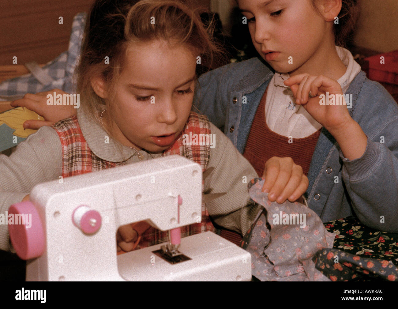Two Girls Side By One Using Sewing Machine