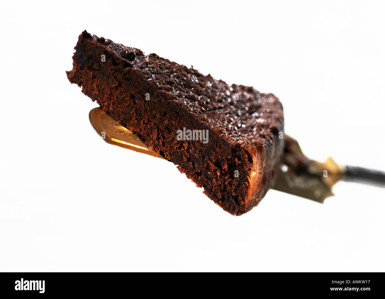 Piece of chocolate cake on cake server, close-up, white background - Stock Image