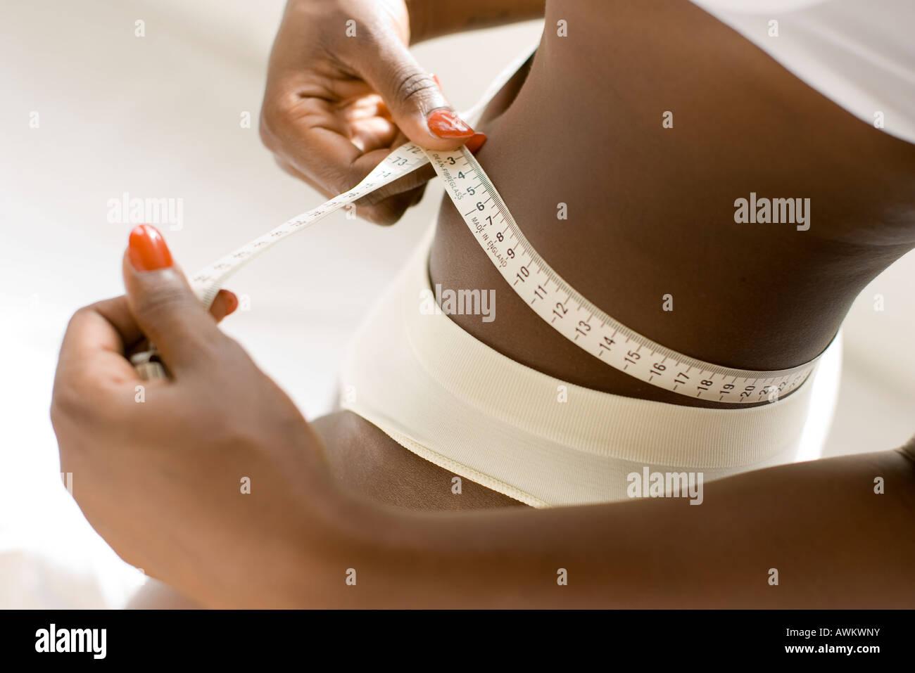ethnic woman measuring her waist - Stock Image