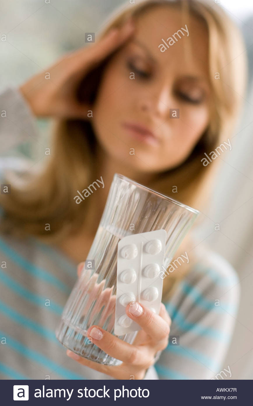 woman with headache holding pills - Stock Image