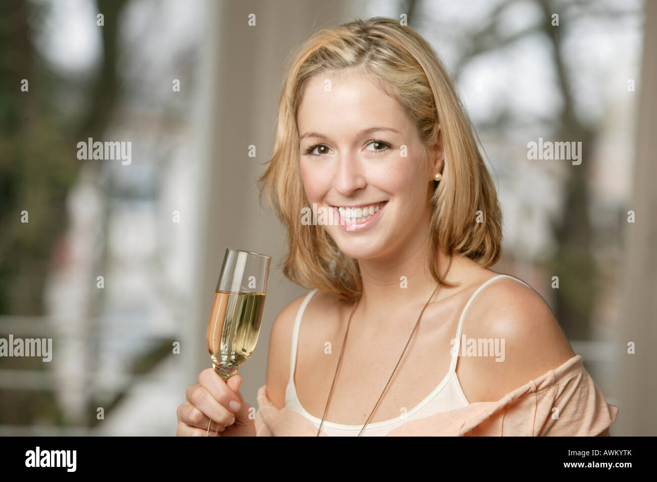 Smiling young blonde woman with champange glass - Stock Image