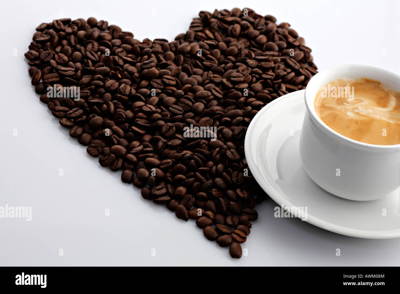 Coffee beans in the shape of a heart beside a cup of coffee Stock Photo