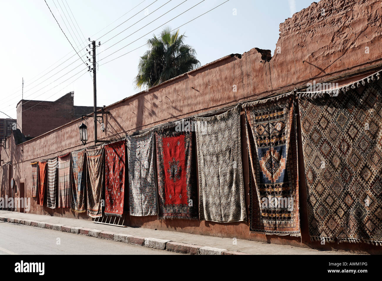 Colourful Berber rugs draped along a long wall in the historic Medina quarter, Marrakesh, Morocco, Africa - Stock Image