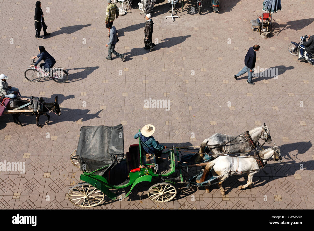 Horse-drawn carriage and pedestrians at Djemaa el-Fna, Marrakech, Morocco, Africa Stock Photo