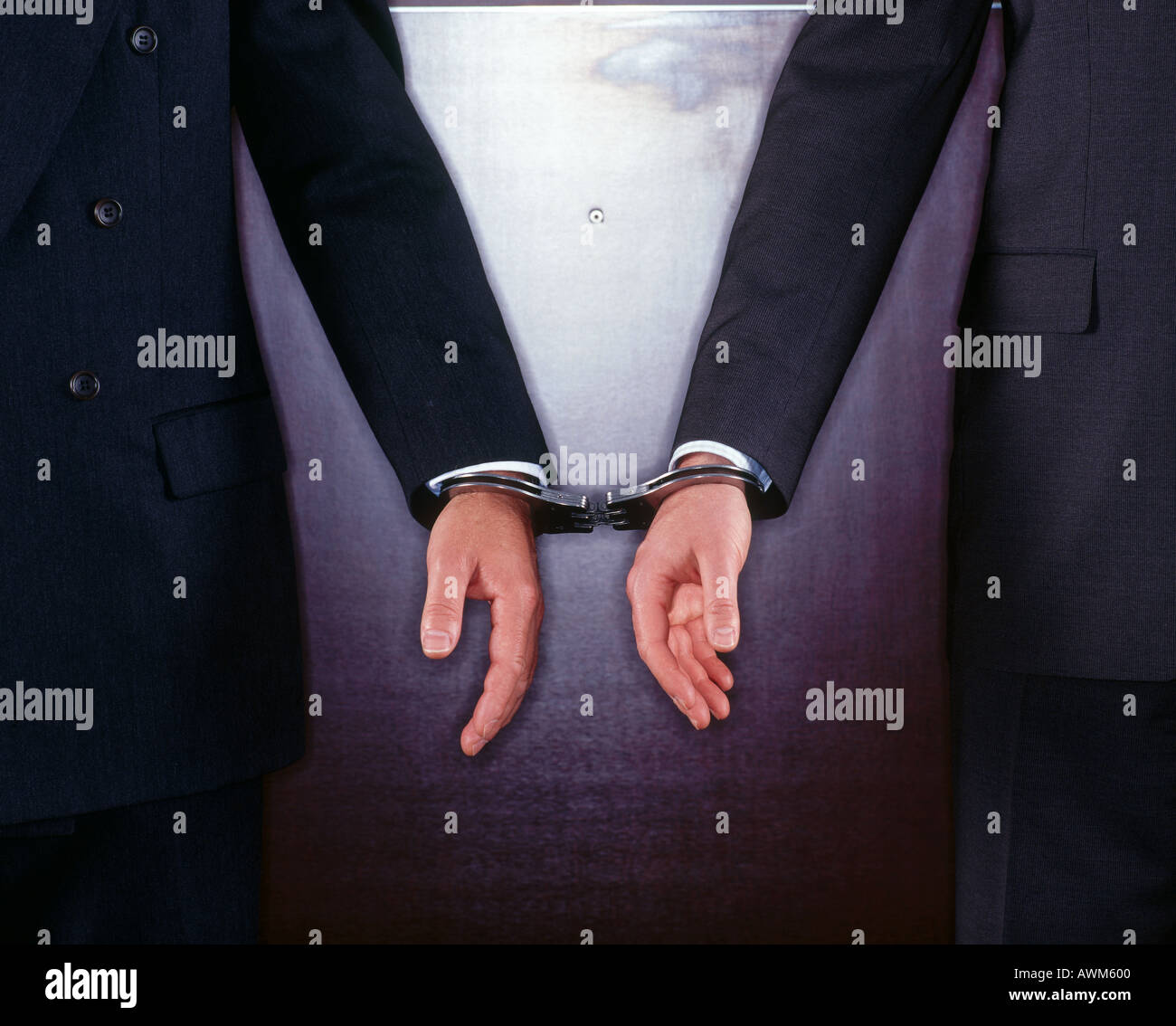Close-up of two businessmen handcuffed together - Stock Image