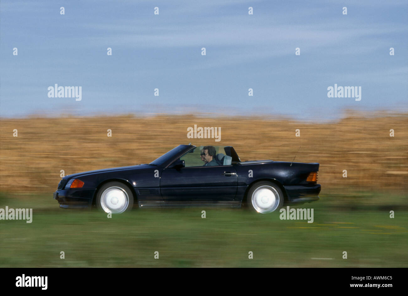 Side profile of man driving convertible car on road - Stock Image