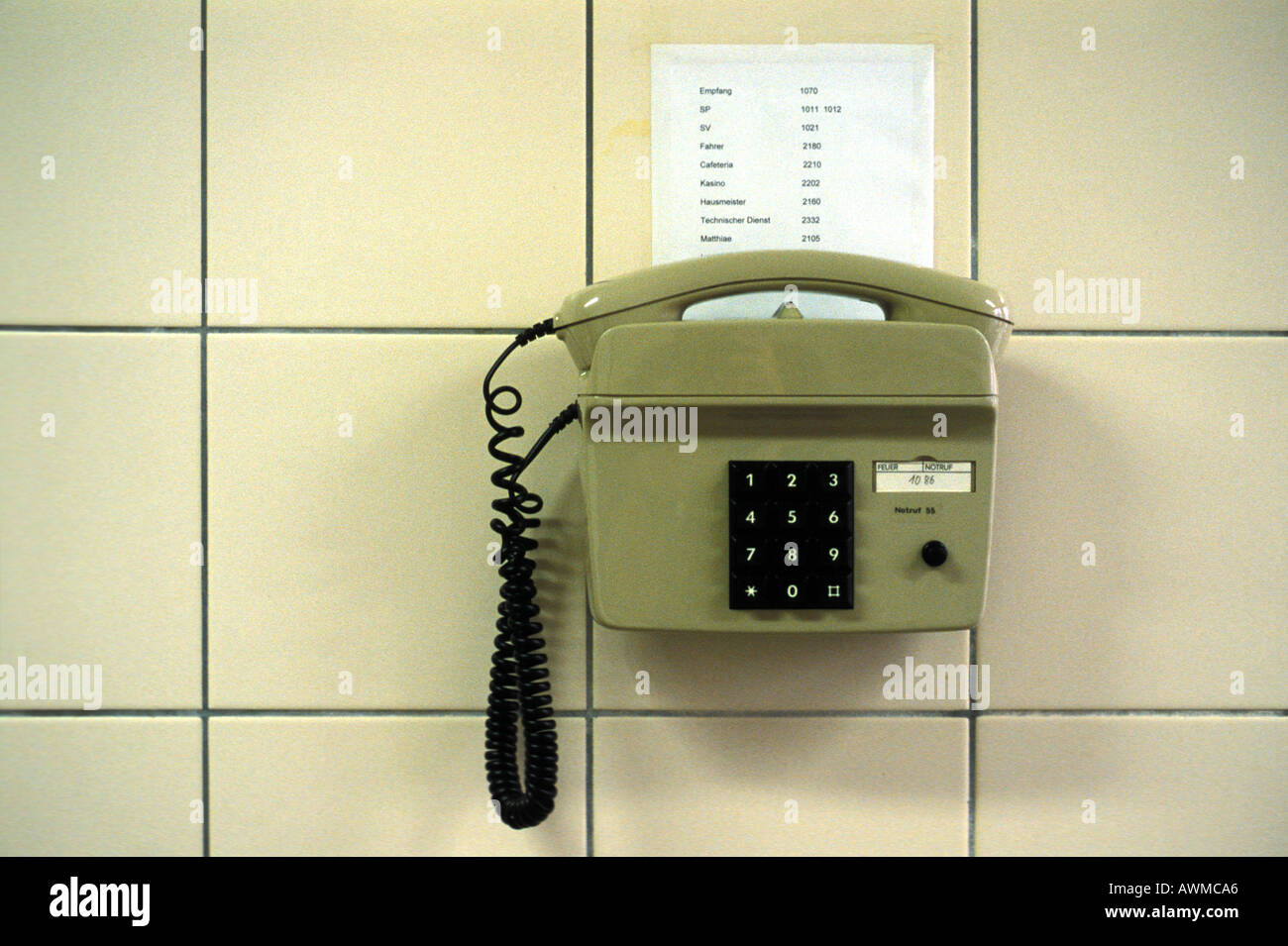 Close-up of phone against tiled wall - Stock Image