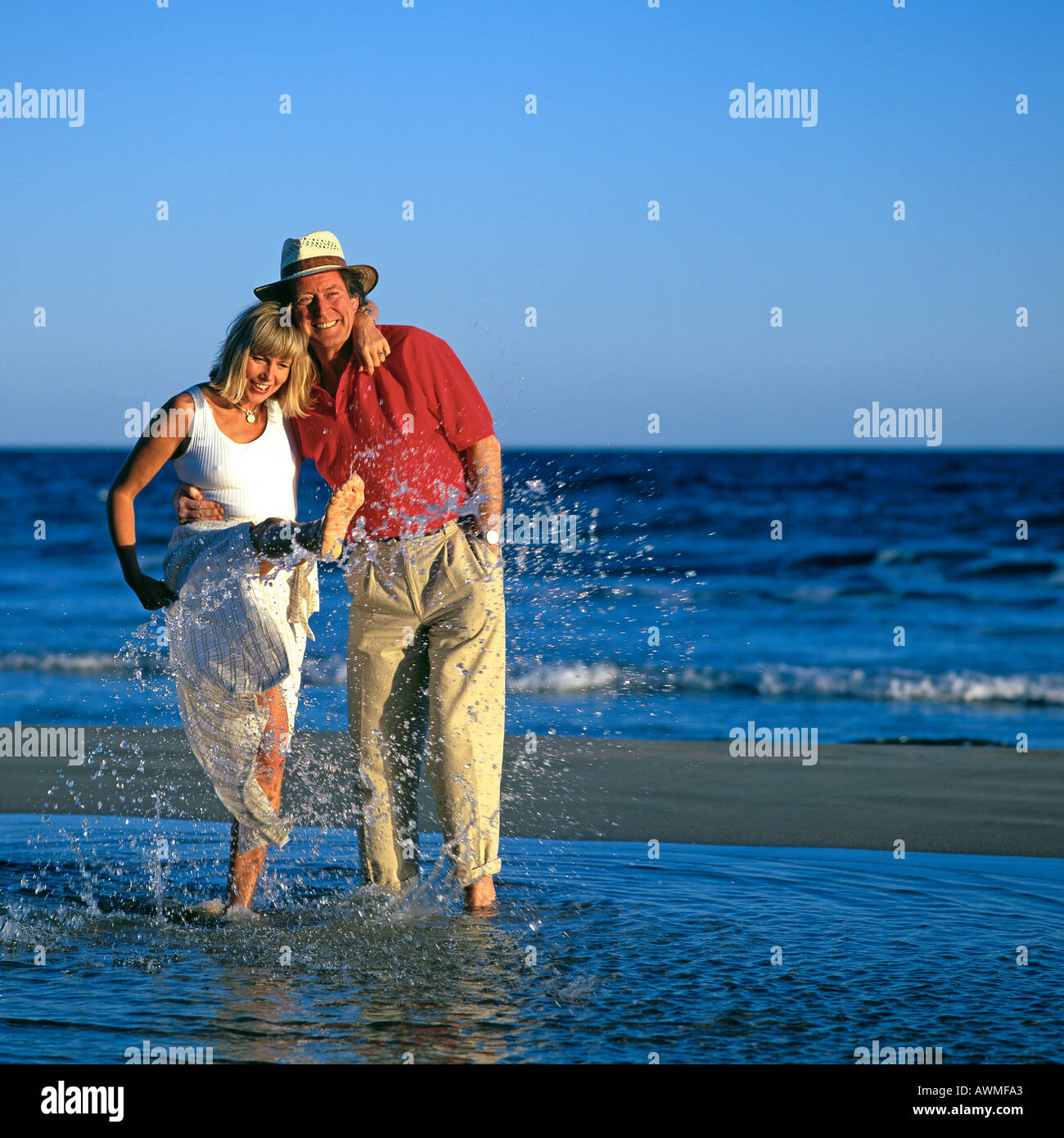 Mature Couple Splashing In Sea Stock Image