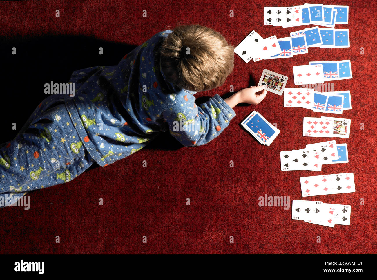 boy laying down and playing cards by himself - Stock Image