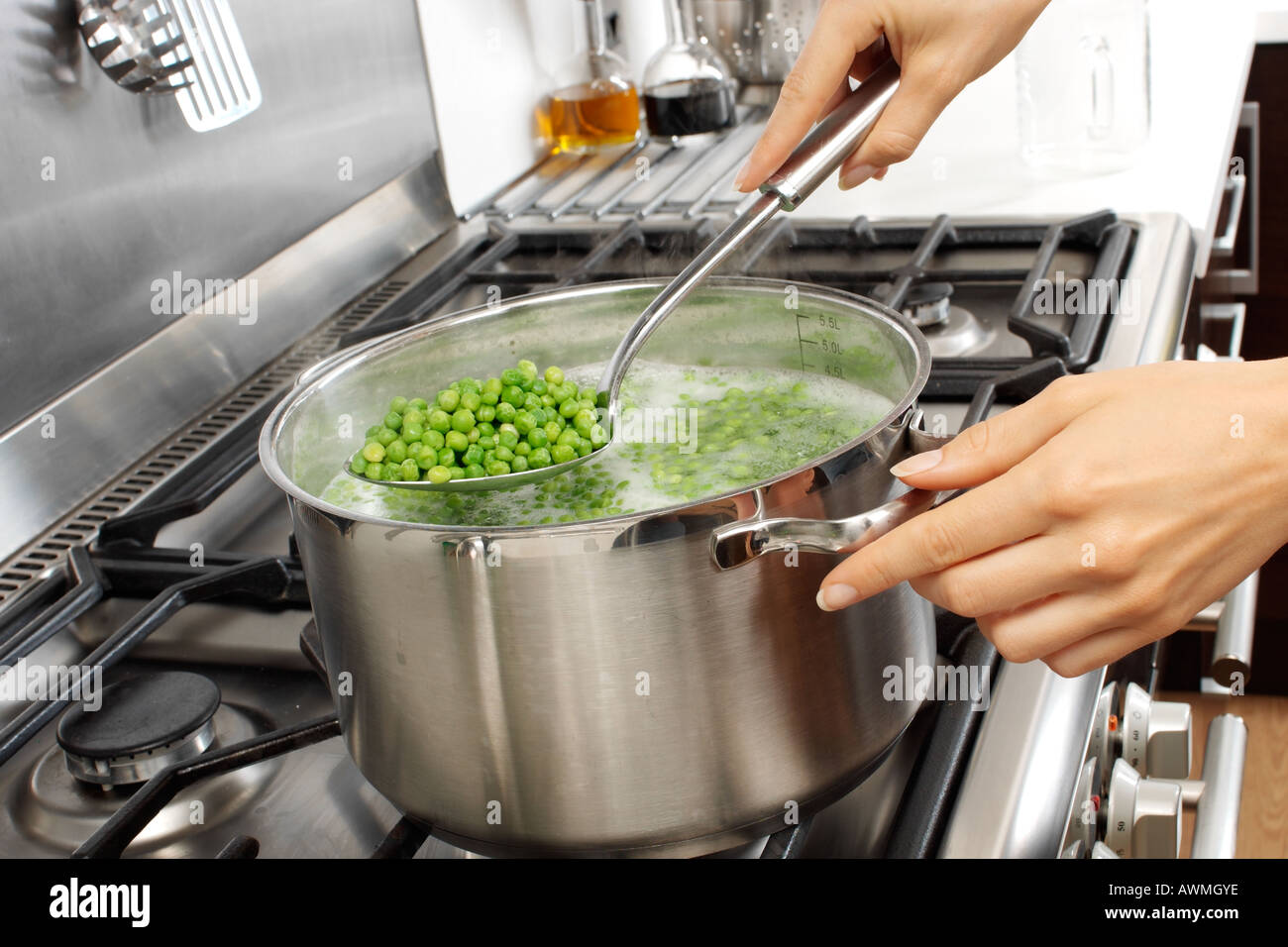 WOMAN IN KITCHEN COOKING PEAS - Stock Image