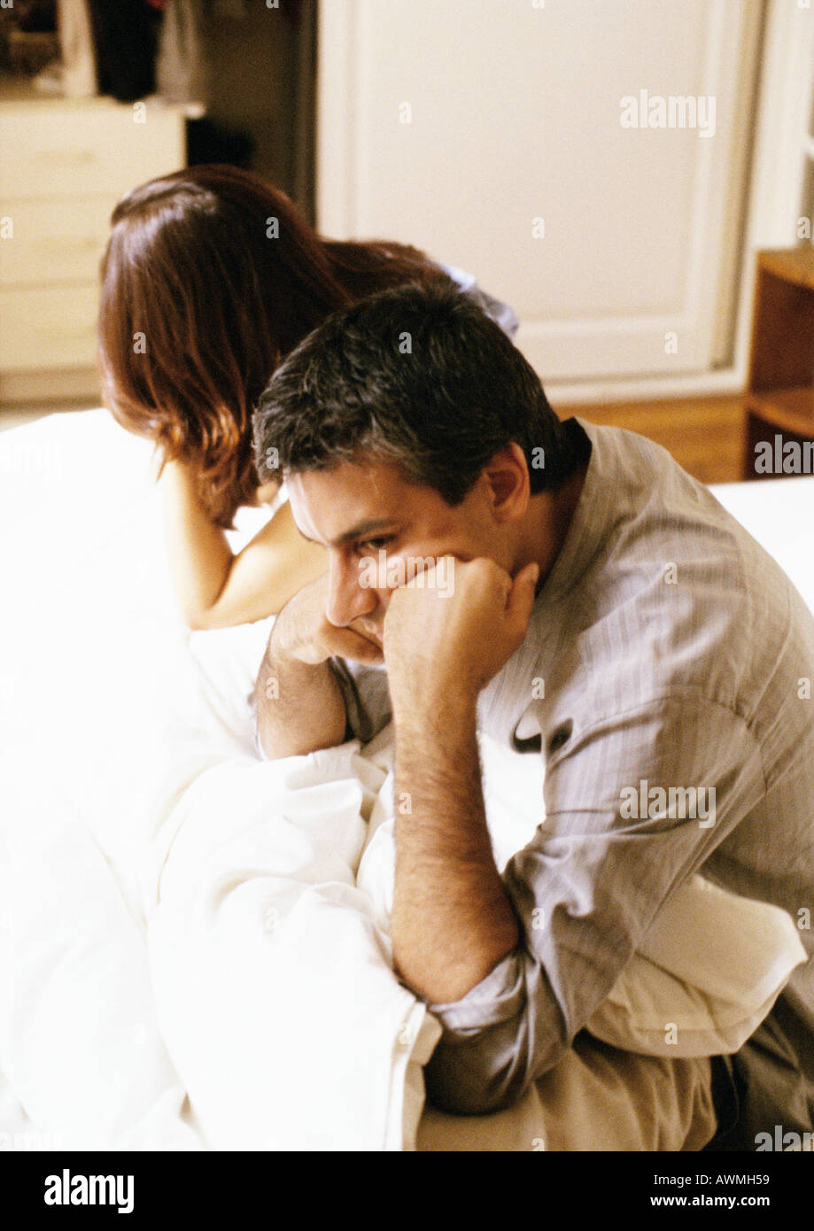Man and woman sitting up in bed, leaning heads on hands, waist up, side view - Stock Image