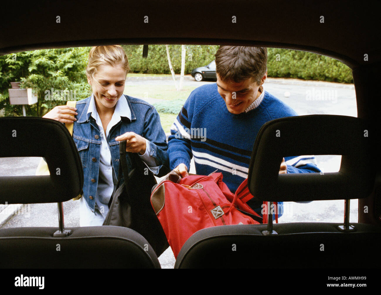 Man and woman putting bags in trunk of car, car headrests in foreground - Stock Image