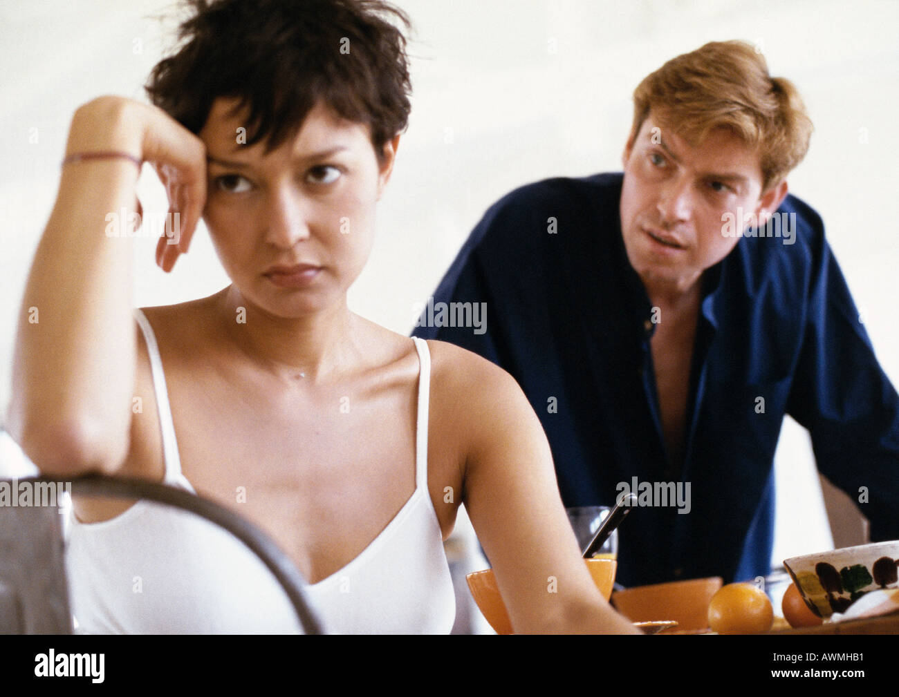 Woman sitting, elbow on back of chair, hand against head, man leaning toward her in background, front view - Stock Image
