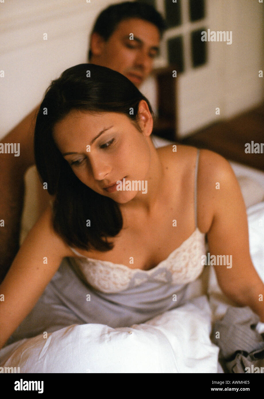 Couple on bed, focus on woman in foreground - Stock Image