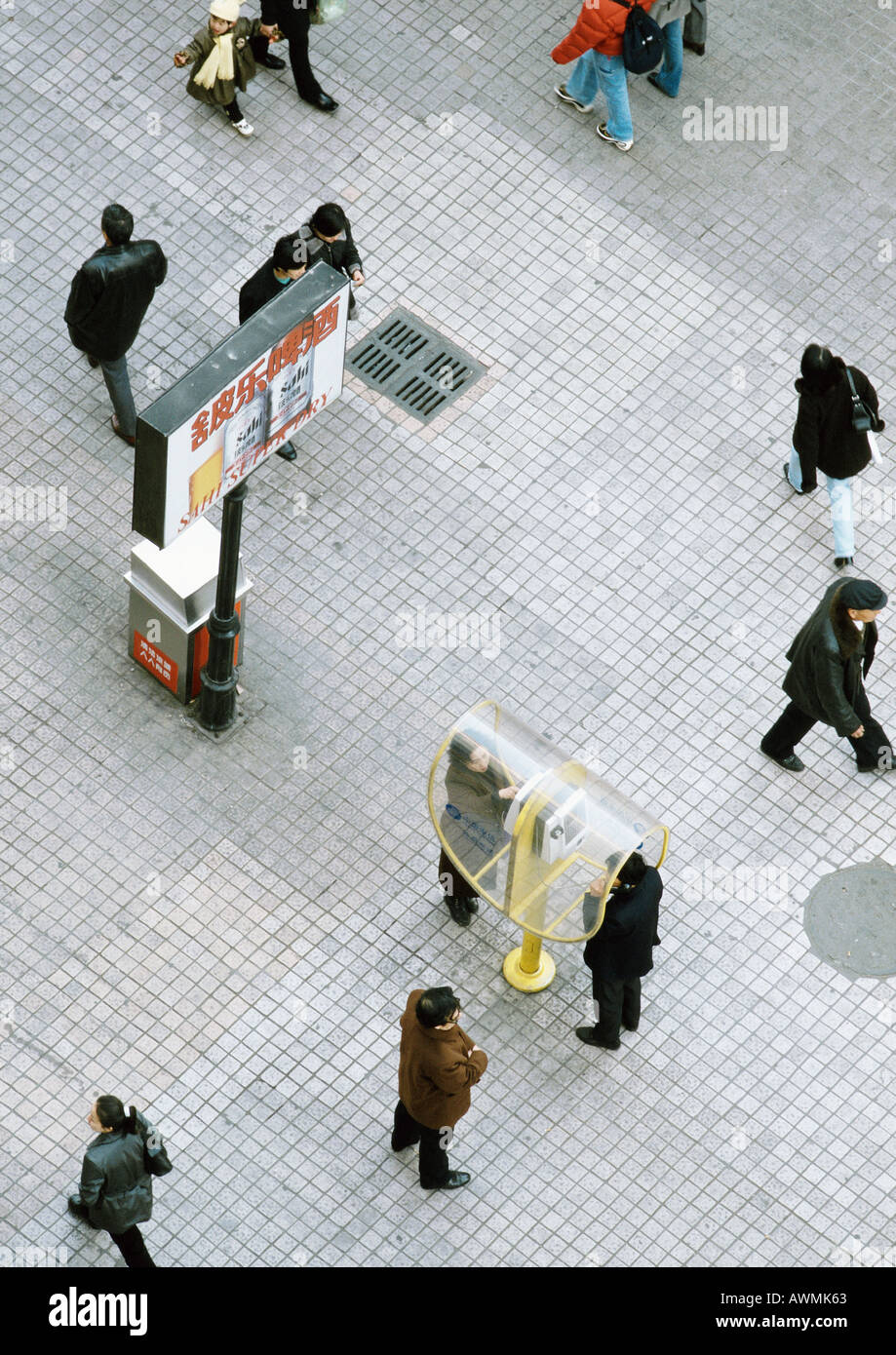 China, Liaoning, Dalian, pedestrians walking across esplanade, people using public pay phones, elevated view - Stock Image