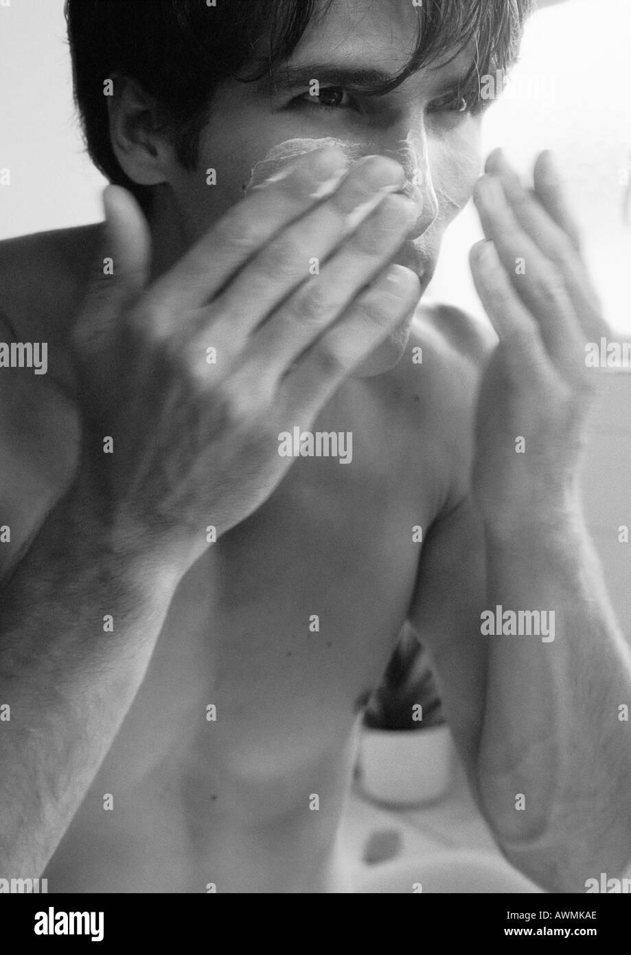 Man putting cream on face, b&w - Stock Image